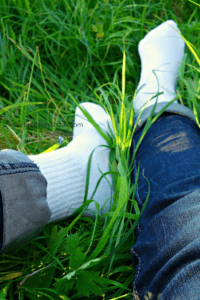 How my hubby can drive me insane - person's legs with jeans and white socks lying on long grass