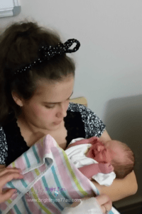 teenage girl holding her newborn baby sister