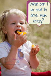 what can I do next to drive mum crazy- why toddlers drive us crazy - toddler girl eating orange pieces