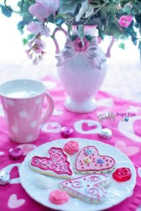heart biscuits on plate, pink flowers in a fancy vase, pink mug with polka dots, hearts on tablecloth