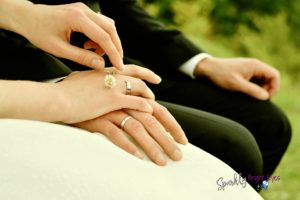 couple holding hands with wedding rings centre of pic