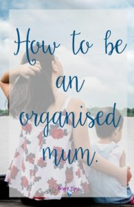 how to be an organised mum - young mother with arms around toddler sitting on a dock looking out to the water